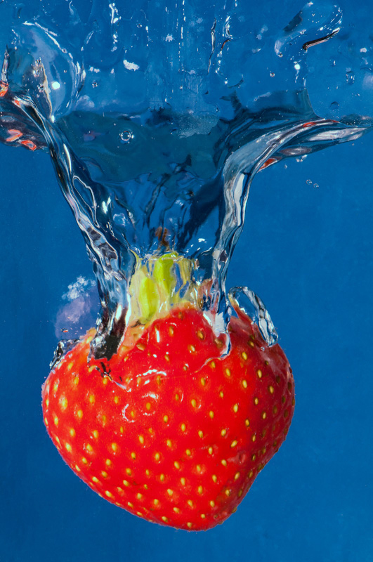 The blue background creates a strong colour contrast with the red strawberry, making it 'pop'