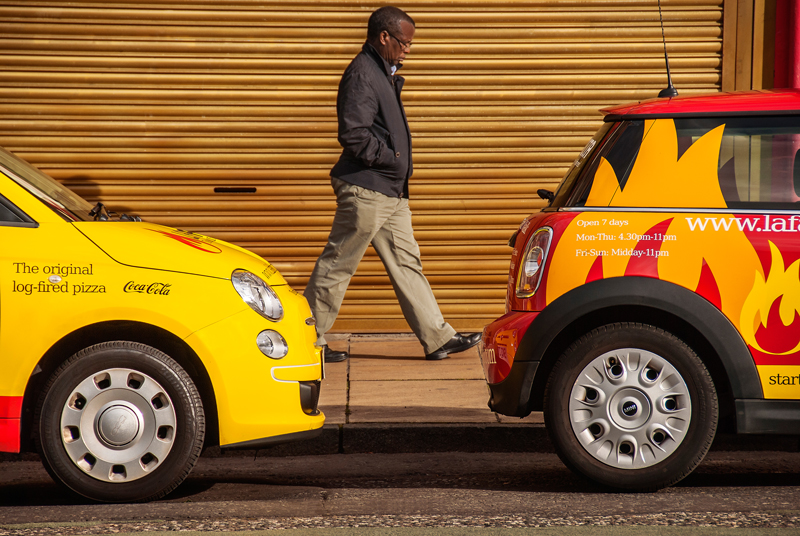 Two brightly coloured cars on Leith Walk, Edinburgh, with a pedestrian