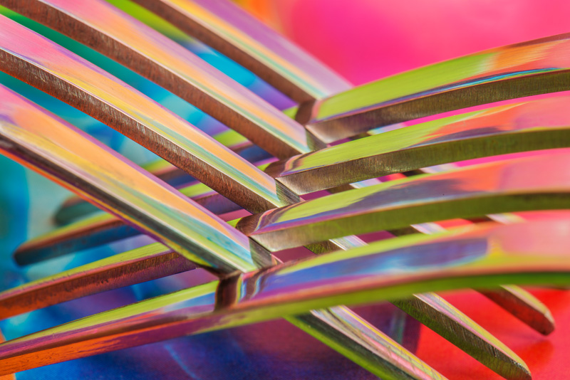 Close-up of forks on colourful background with reflections