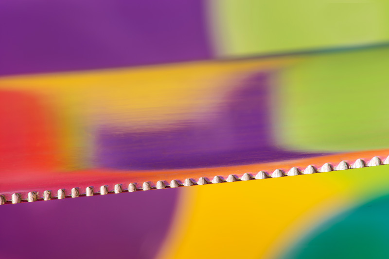 Close-up of kitchen knife on a colourful background with reflections