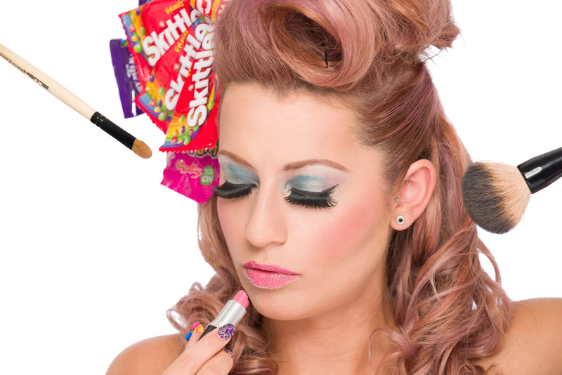 Beauty model with candy girl themed hair, makeup and nail with lipstick and makeup brushes,.
