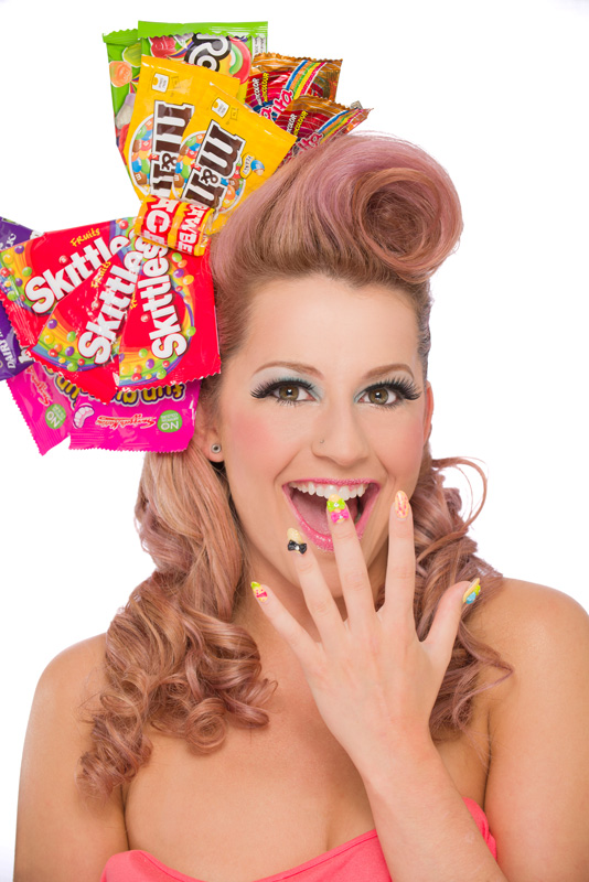 Beauty model with candy girl themed hair, makeup and nails showing off her dazzling smile and nails.