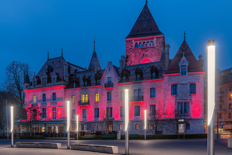 Ouchy Castle Hotel in Lausanne Switzerland, night photograph with the Castle illuminated in red.