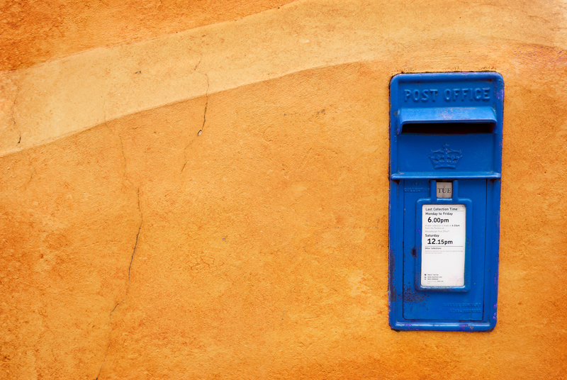 Musselburgh mailbox on an orange wall. The colour of the mailbox was changed from red to blue