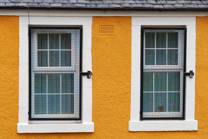 Couple of windows on an orange wall in Musselburgh