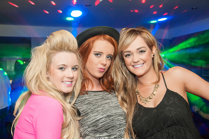 Three young ladies posing for the camera in front  of the club lights at Madisons night club, Musselburgh