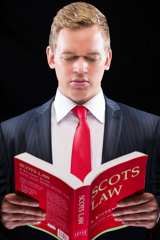 Portrait of Mark McLeod of Scotia Accounting against a black background and holding a 'Scots Law' red book.
