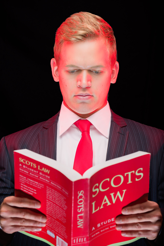 Portrait of Mark McLeod of Scotia Accounting against a black background and holding a red 'Scots Law' book. Two of the lights are coloured red.