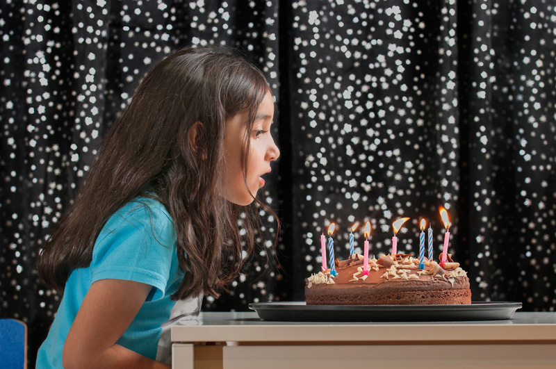 Young girl blowing out the candles on her birthday cake