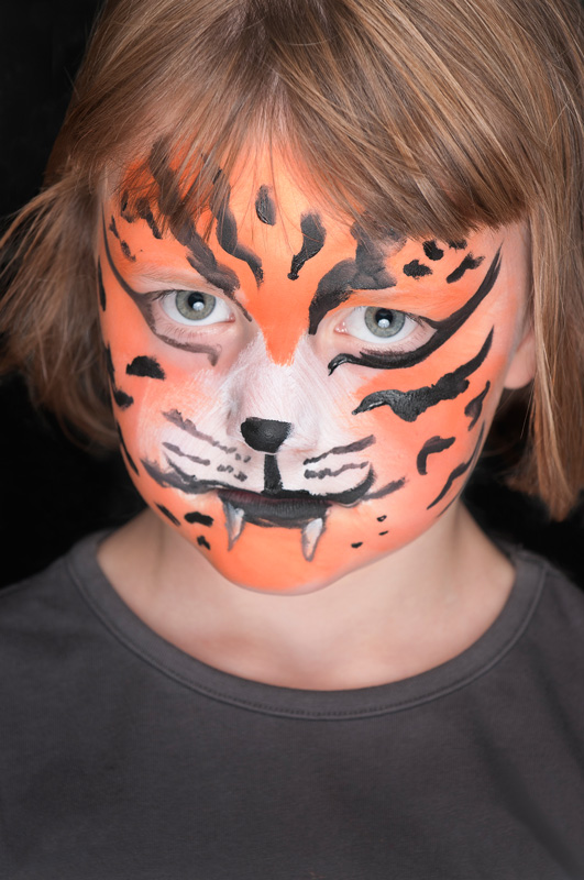 Young girl with her face painted to look like a tiger