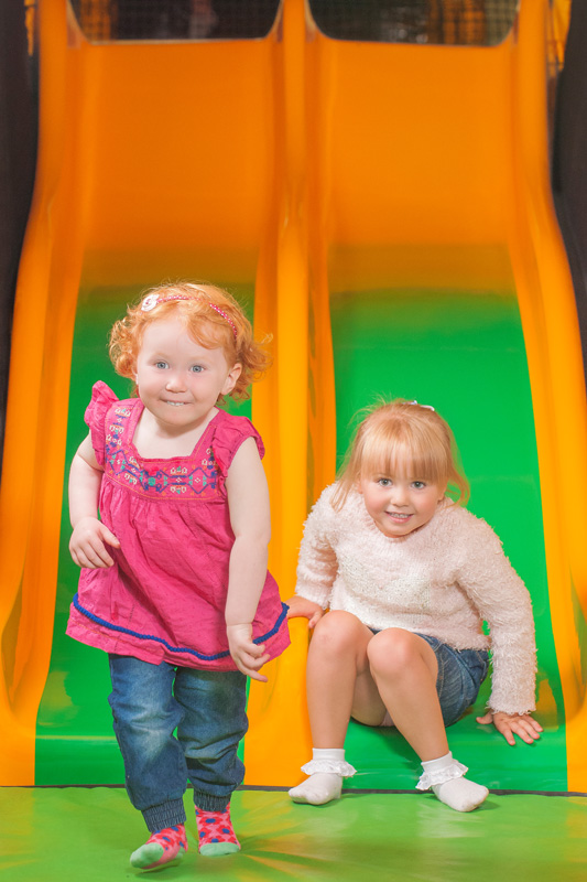 Two young girls on a small slide