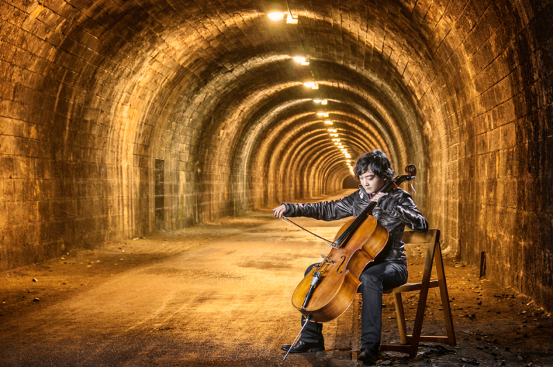 Composer Atzi playing the cello inside the Innocent Railway tunnel in Edinburgh