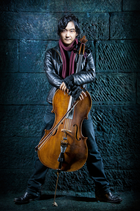Composer Atzi standing against a wall holding his cello., inside the Innocent Railway tunnel, Edinburgh