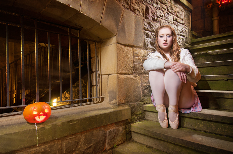 Classical dancer on stairs with carved pumpkin, on Halloween night in Edinburgh, Scotland
