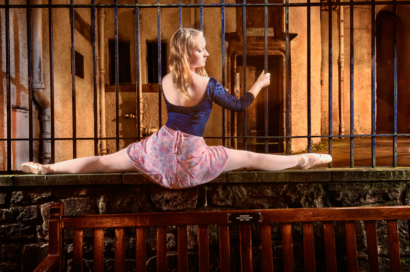classical dancer doing the splits on a short wall off the Royal Mile in Edinburgh, Scotland