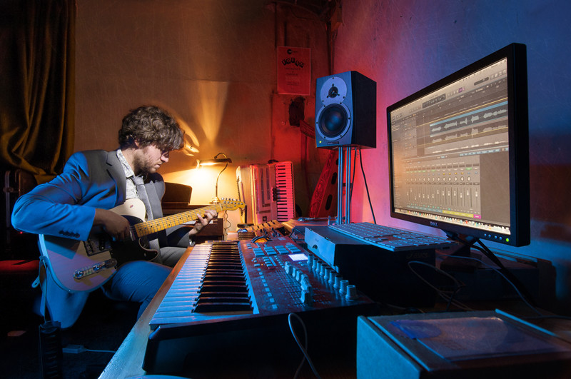 Light painting of composer and audio producer Frankie Lowe  in his studio playing the guitar.