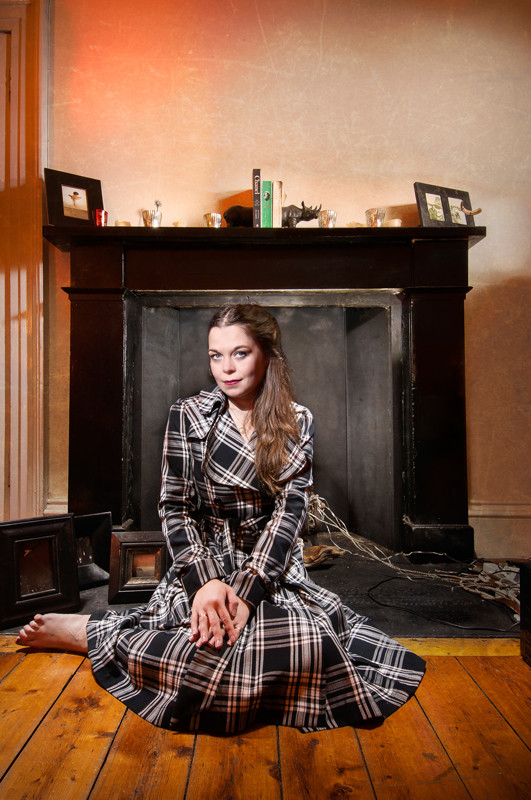 Light painting of actress, writer and performer Juliette Burton sitting in front of  the fireplace in her Edinburgh flat