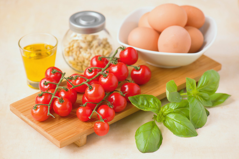 Raw ingredients, olive oil, basil, eggs and tomatoes.