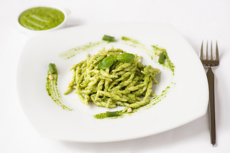 Plate of freshly made pesto pasta on white tablecloth