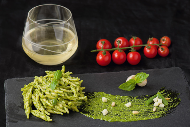 Pesto pasta on a slate with a glass of white wine and tomatoes