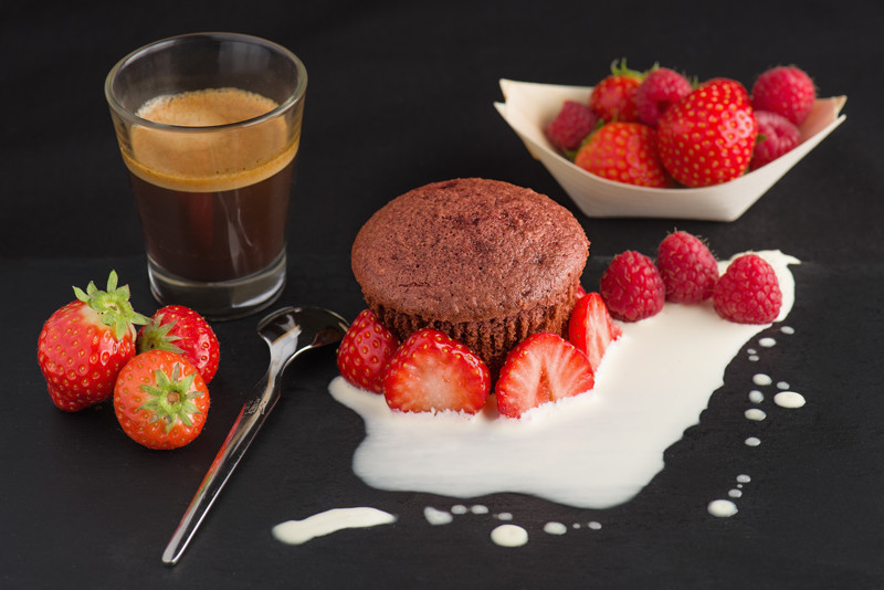 Red velvet cupcake with cream, strawberries and some Italian coffee on a black slate.