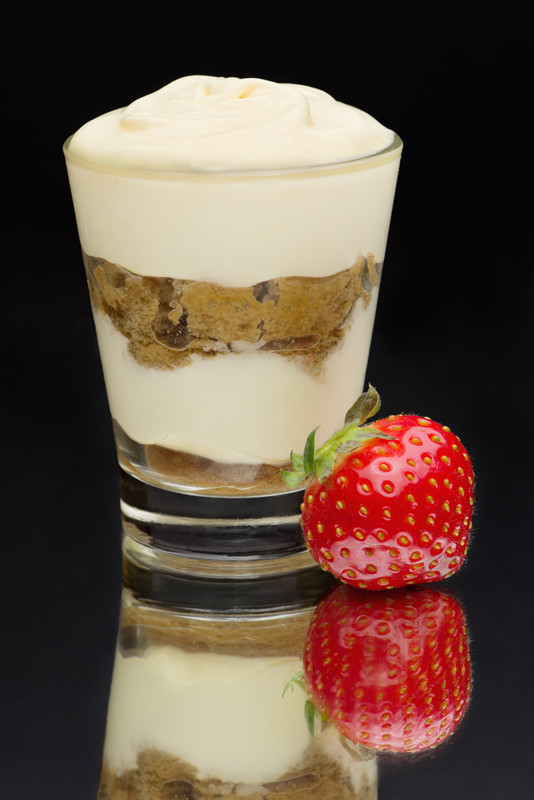Tiramisu in a glass with strawberry on a mirror