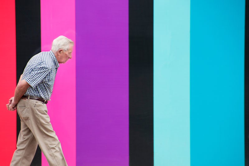 Older gentleman walking in front of a very colourful wall  in Edinburgh, Scotland