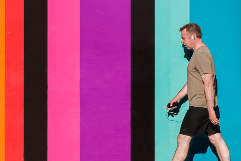 Gentleman with an iPod or other mp3 player walking in front of a colourful wall in Edinburgh, Scotland