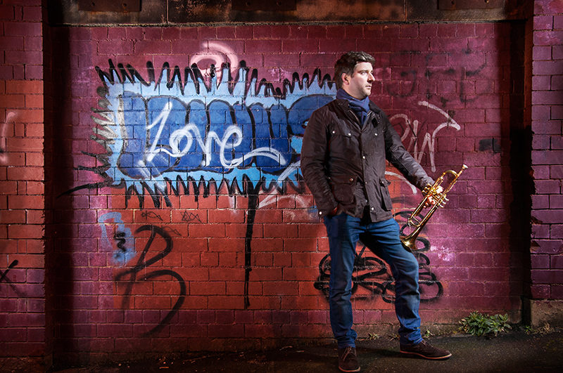 Light painting of musician and education Finlay Hetherington in front of a graffiti wall with his trumpet