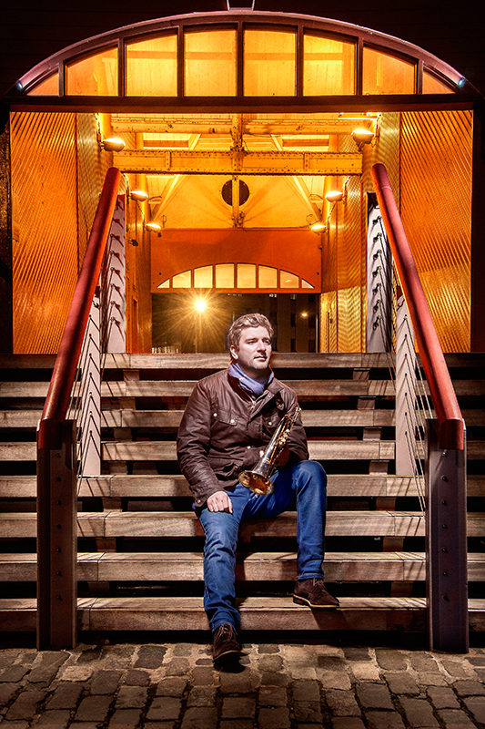 Light painting of musician and educator Finlay Hetherington with his trumpet sitting on a flight of stairs in an urban location