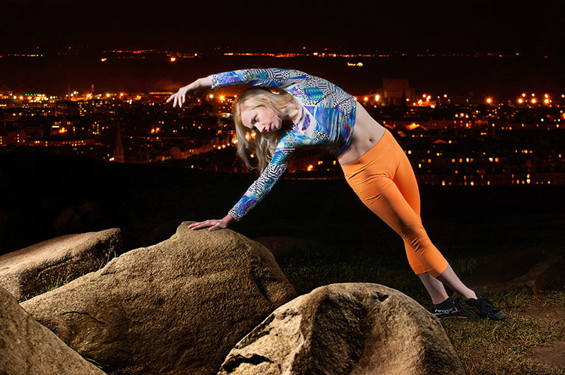 Light painting of dancer on Calton Hill with the city of Edinburgh as backdrop