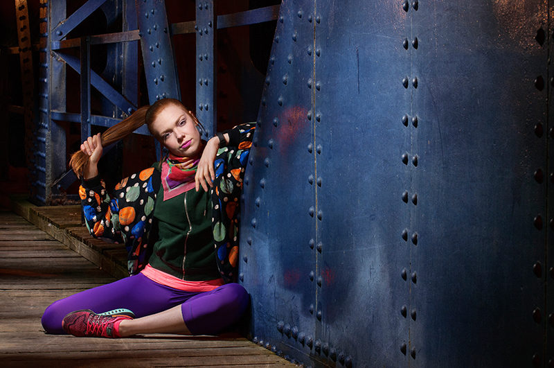 Light painting of dancer, sitting down, with a blue steel bridge in Leith, Edinburgh