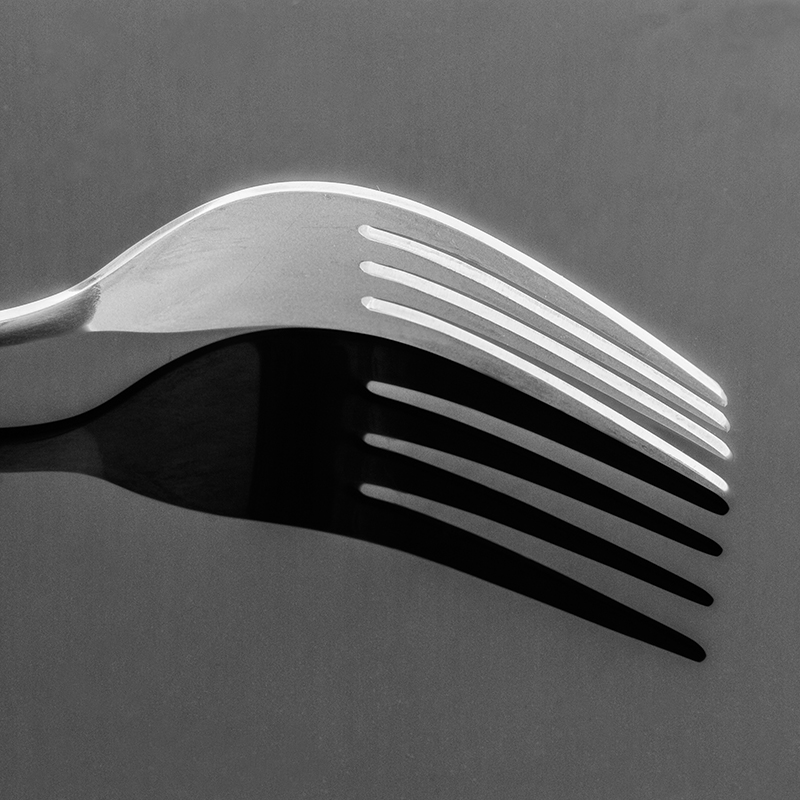 Black and white picture of the fork on a black pice of plexiglass