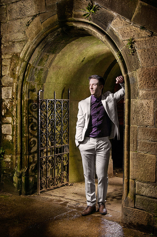 Light painting of male dancer wearing a suit and framed with one arch of McKenzie bridge, in Stockbridge, Edinburgh