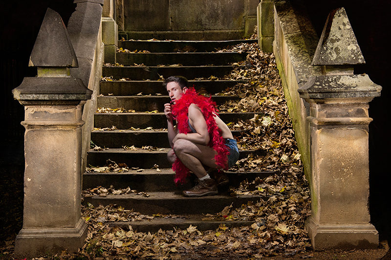 Light painting of dancer wearing jeans hot pants and a red boa at McKenzie bridge, Stockbridge, Edinburgh
