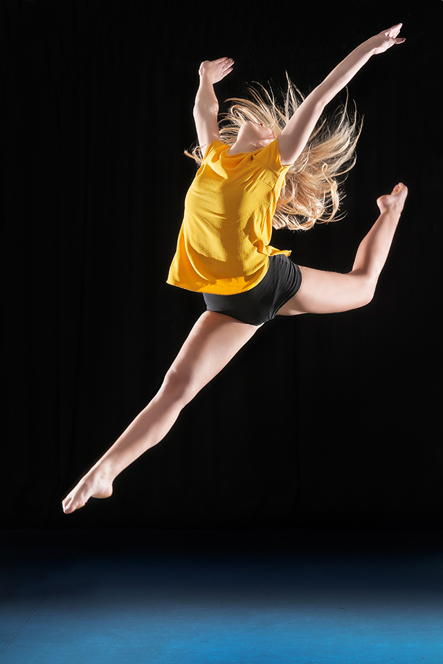 Jumping dancer in front of black background in a dance studio