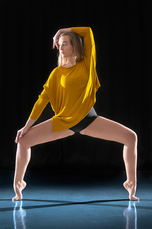 Dancer posing in front of back background in a dance studio.