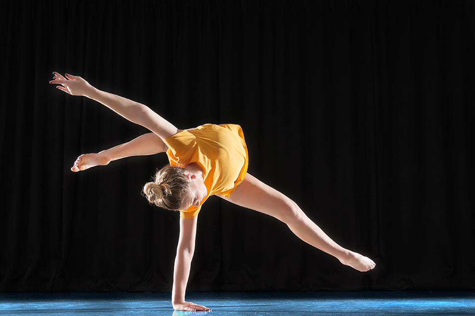 Dancer acrobatics in front of a black background in a dance studio