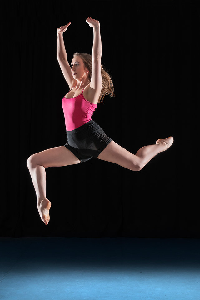 Dancer jumping in front of a black background in a dance studio.