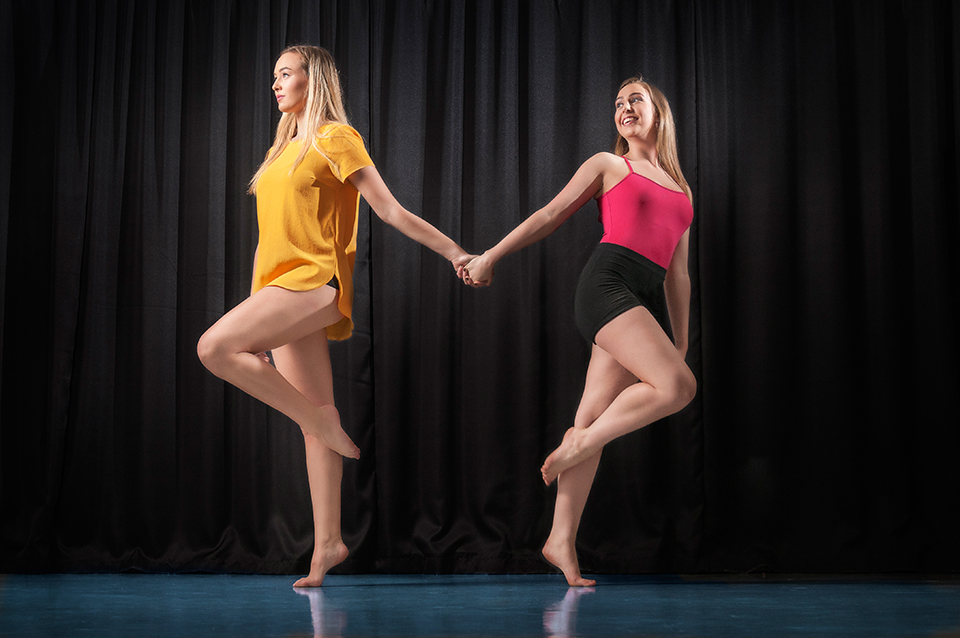 Two dancers holding hands in front of black background in a dance studio.
