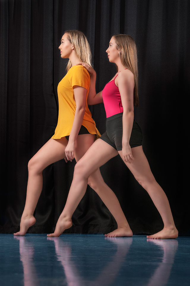 Two dancers in front of black background in a dance studio